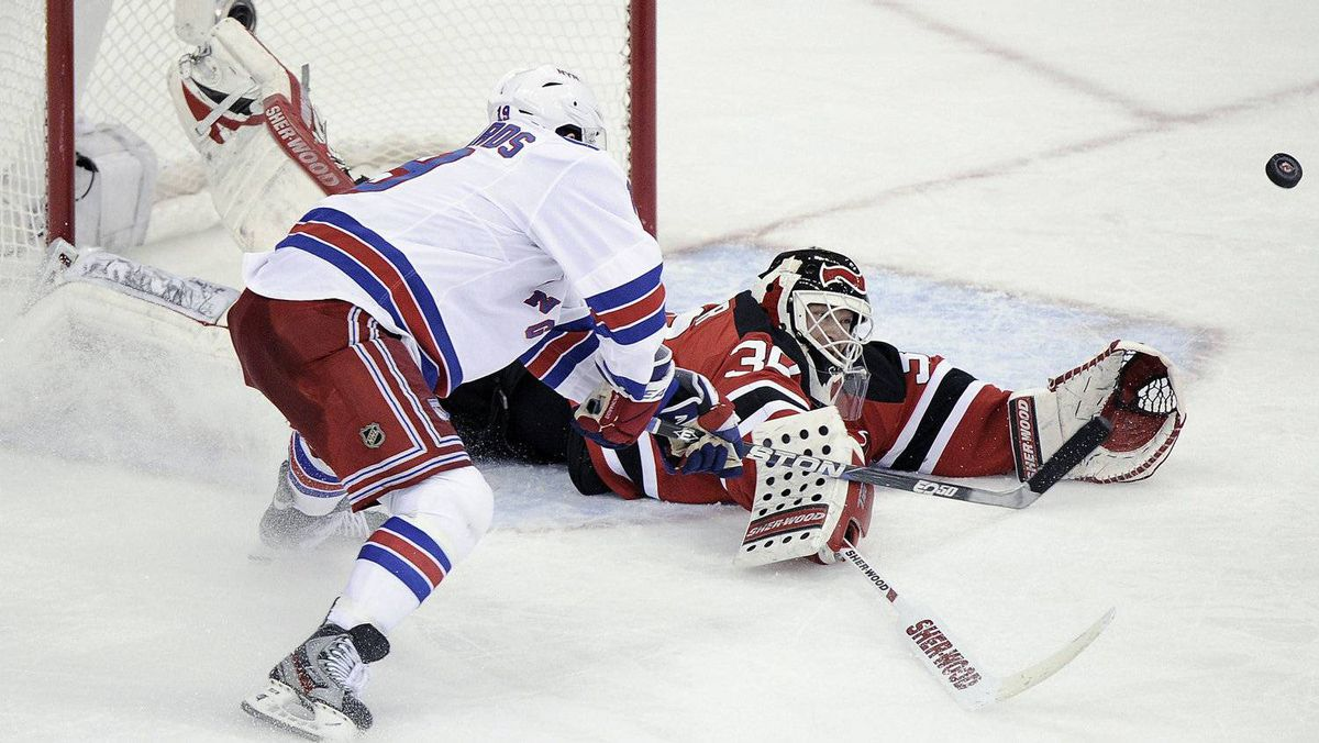 New Jersey Devils goalie Martin Brodeur (R) makes a save on New York Rangers' Brad Richards during the second period in Game 3 of their NHL Eastern Conference Final in Newark, New Jersey, May 19, 2012.