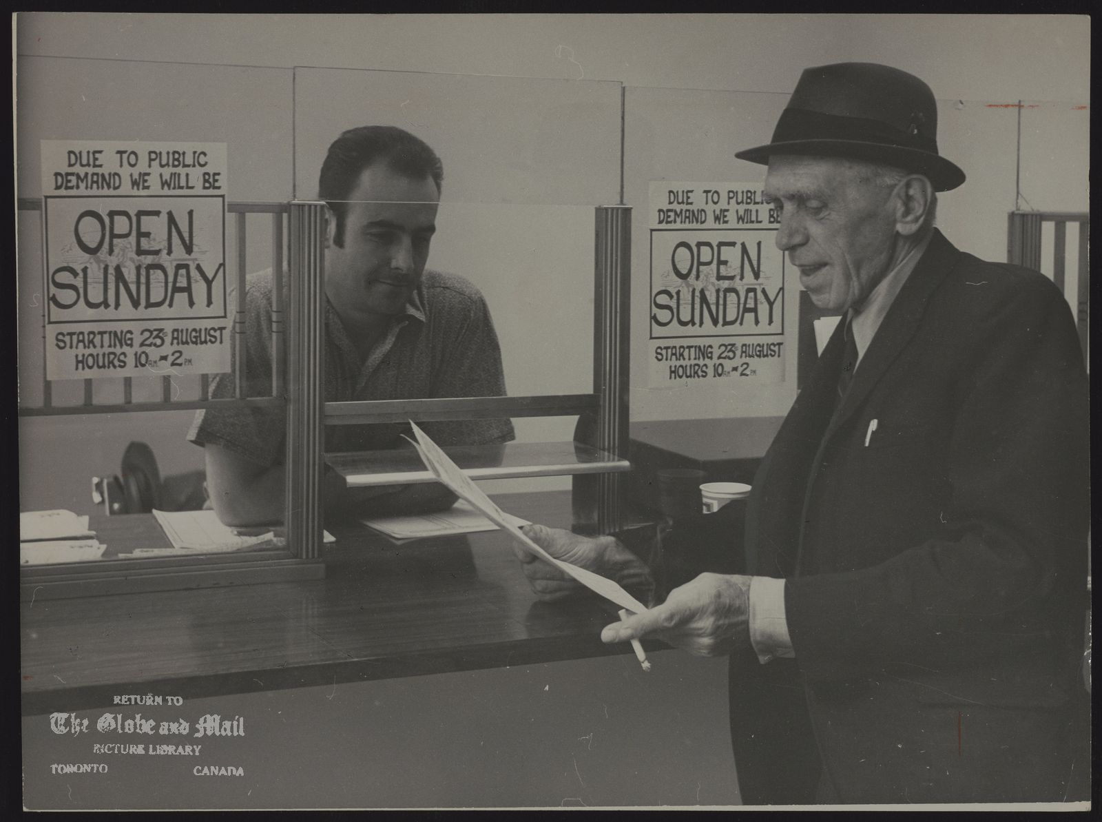 The notes transcribed from the back of this photograph are as follows: Emil Kalix, 66 looks at a winner before placing his bet with payout clerk Jim Paterson, 32, at a betting shop on King Street. Twenty-one Metro shops were opened on Sunday for first time yesterday