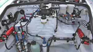 The front compartment of the GT3 Cup is filled with plumbing for the car's systems. The white cylinder in the center (with blue cap) is an air jack that lets mechanics raise the car in seconds. The light-green bottle next to it is the fluid reservoir for the electrically-driven power steering. The silver canisters on the bottom left are high-pressure pumps for the fuel-injection system. The horizontally-mounted red cylinders on the left and right are remote air and fluid reservoirs for the front shock absorbers. The black aluminum component at top (with two holes in it) is a quick-fill port for the fuel tank. To the right of the quick filler are two hydraulic cylinders that work the brakes.