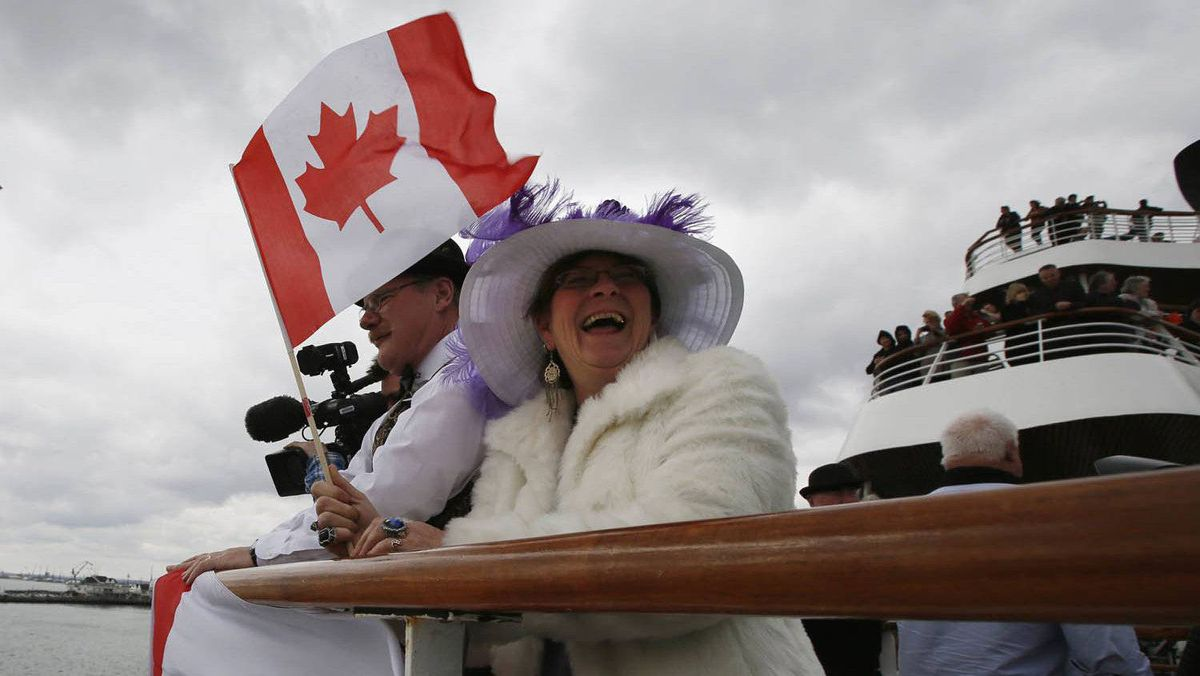 Bernadette and Brice Christie of Grande Prairie, Alberta stand with Canadian flags as the Titanic Memorial Cruise leaves port in Southampton, England April 8, 2012.