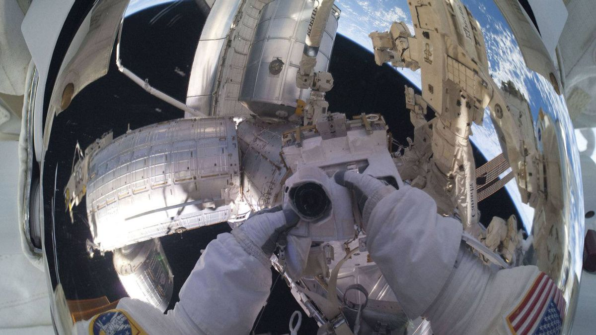 NASA spacewalker Mike Fossum's helmet visor mirrors a panoramic scene of the docked International Space Station with the space shuttle Atlantis and the blue and white Earth below in this photo provided by NASA and taken July 12, 2011.
