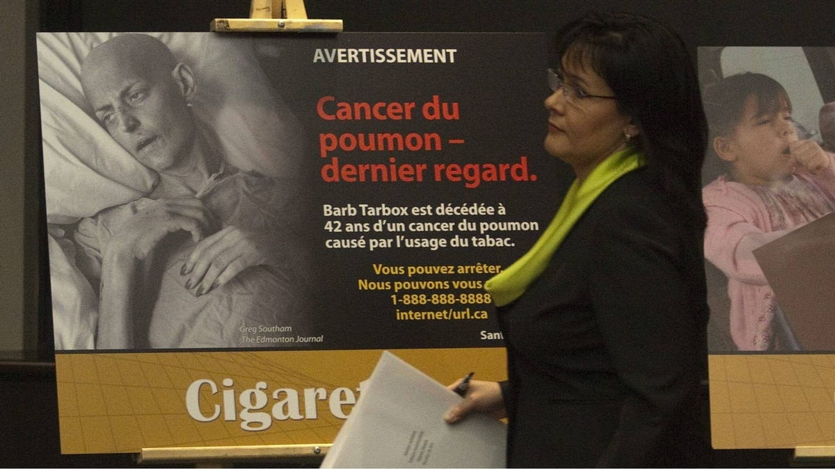 Health Minister Leona Aglukkaq walks past a new cigarette packaging image of lung cancer victim Barb Tarbox during a news conference in Ottawa on Thursday, Dec. 30, 2010. The government has introduced new cigarette packaging images to fight smoking among Canadians.
