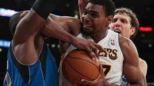 Los Angeles Lakers center Andrew Bynum, middle, battles to keep the ball from Dallas Mavericks center Brendan Haywood, left, and Mavericks forward Dirk Nowitzki during the second half of an NBA basketball game, Sunday, April 15, 2012, in Los Angeles. The Lakers won 112-108. (AP Photo/Bret Hartman)
