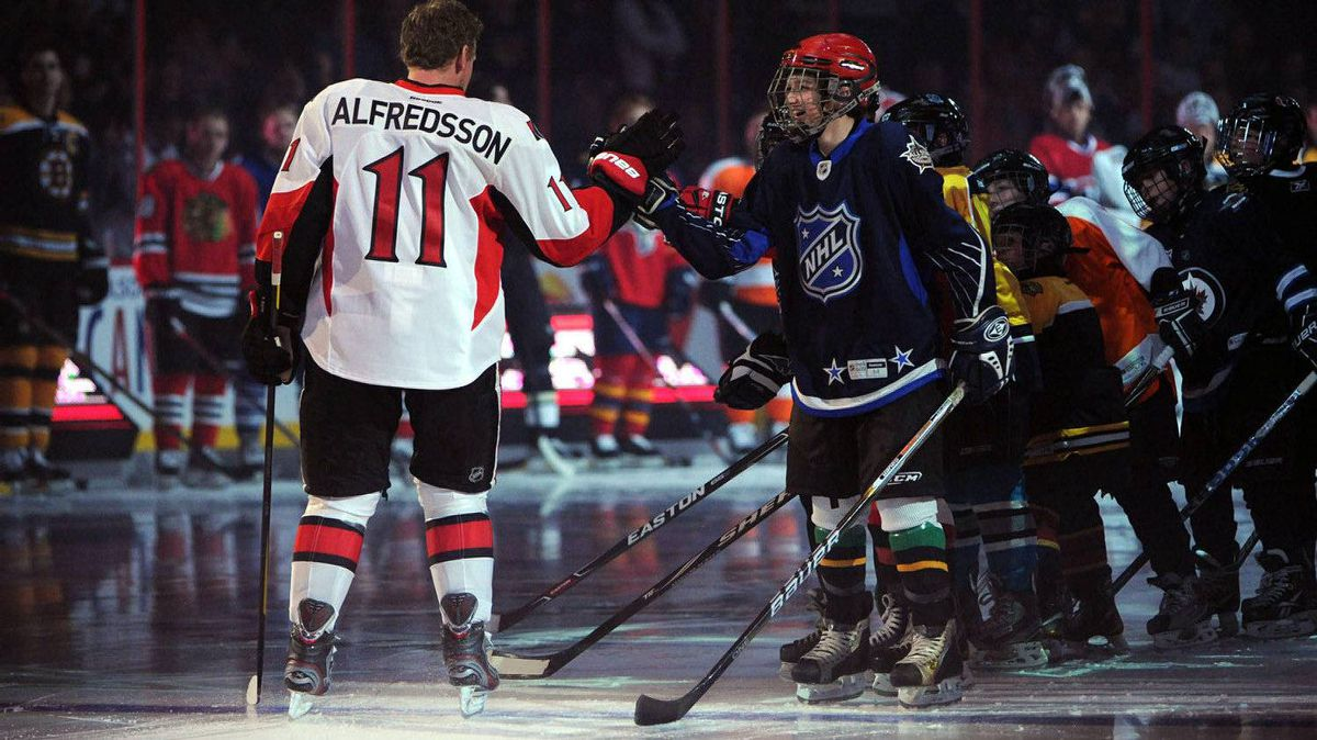 Ottawa Senators' Daniel Alfredsson gives a group of young hockey players high-fives as he makes his way onto the ice during the NHL All-Star skills competition in Ottawa on Saturday, January 28, 2012. THE CANADIAN PRESS/Sean Kilpatrick