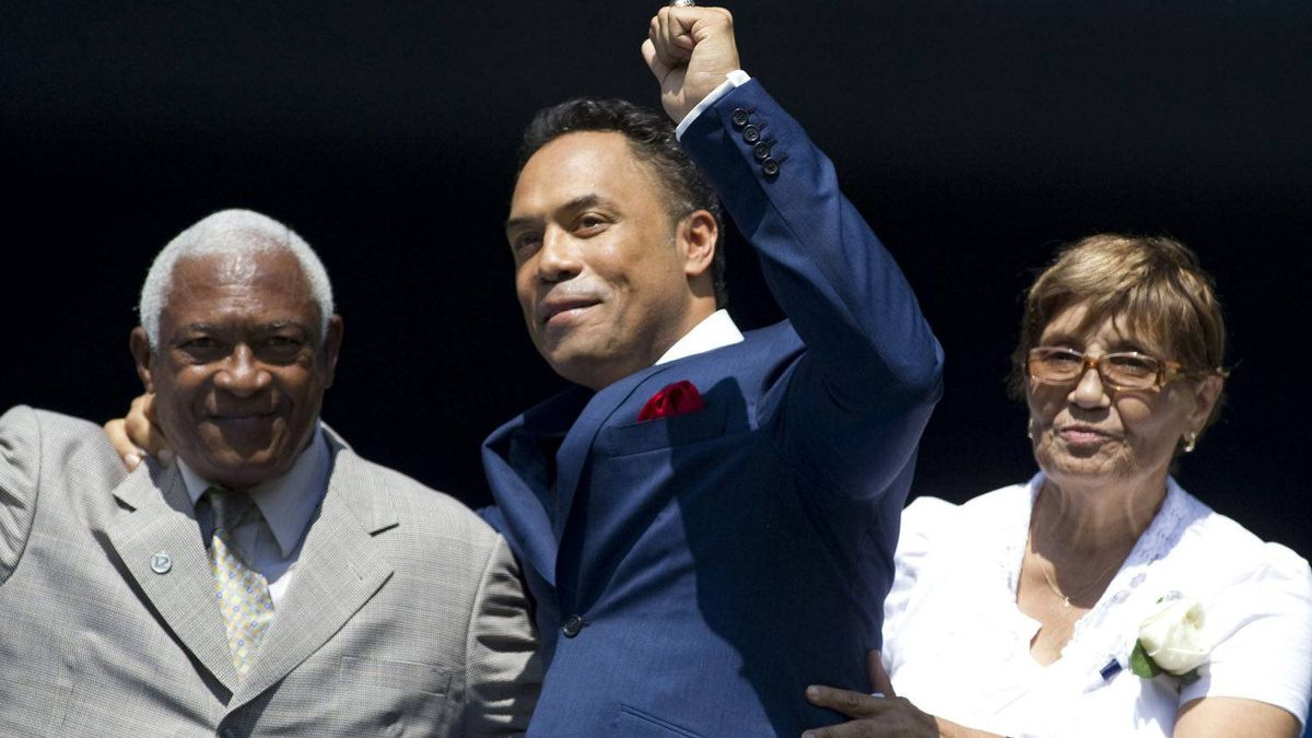 Roberto Alomar (centre) gestures to the crowd as he stands with his father Roberto Sr.(right) and mother Maria as his number is retired. THE CANADIAN PRESS/Chris Young