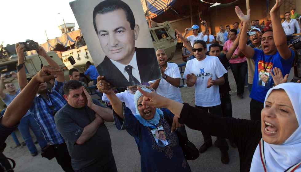 Supporters of ousted Egyptian President Hosni Mubarak hold his picture and shout slogans outside the police academy where Mubarak's trial is held on the outskirt of Cairo.