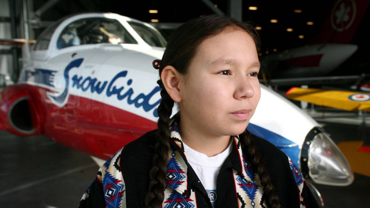 Kenzie Wilson of Clear Lake, MB poses for a photograph next to a Canadair CT-114 Tutor (Snowbirds) at the Museum of Aviation in Ottawa on November 21, 2011.