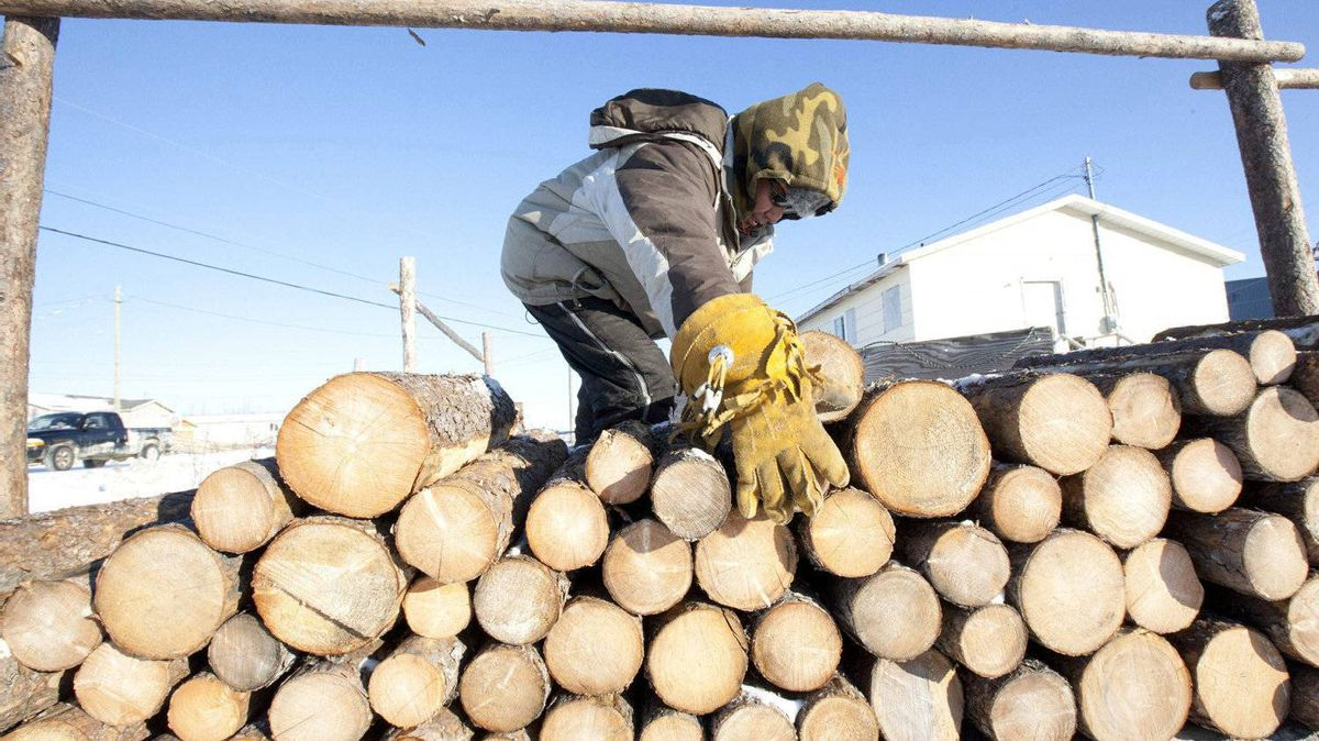 Samuel Metat moves firewood which he sells to residents in Attawapiskat, Ont., Tuesday November 29, 2011. Prices for firewood range from $150-$200 per cord.