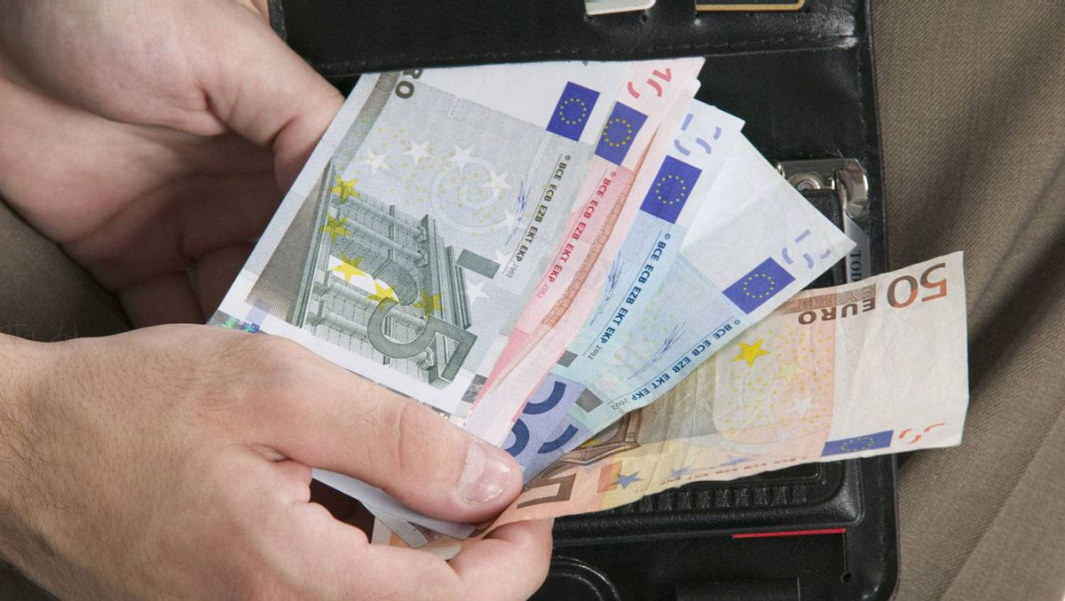 Close-up of hand holding euros by a wallet
