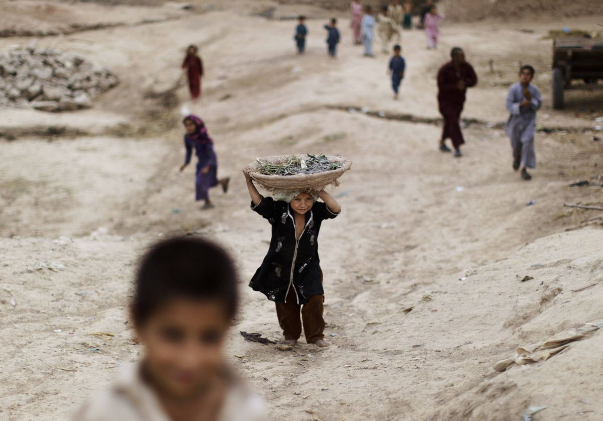 An Afghan refugee girl, center, returns home carrying a basket on her head in a slum area on the outskirts of Islamabad, Pakistan.