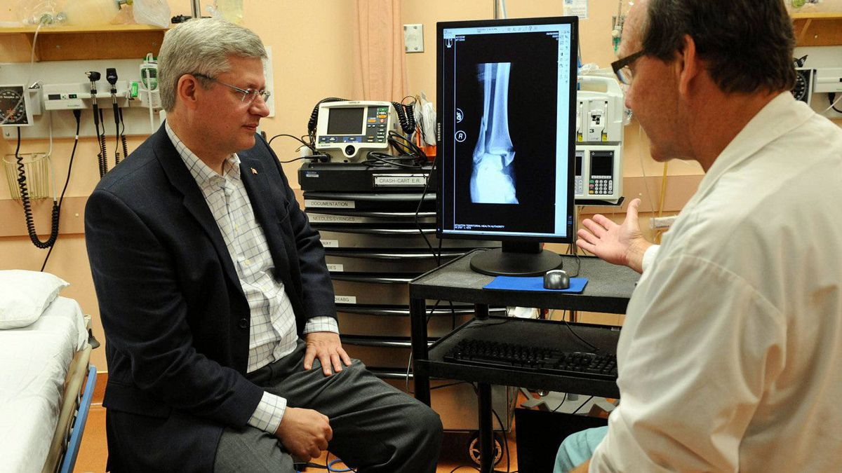 Prime Minister Stephen Harper speaks with a physician at Yellowknife's Stanton Hospital on Aug. 25, 2011.