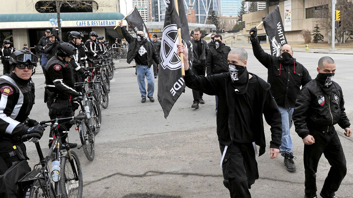 White supremacists walk past a police line during their rally in downtown Calgary on Saturday, March 19, 2011. Police kept them apart from another group holding an anti-racist demonstration nearby.