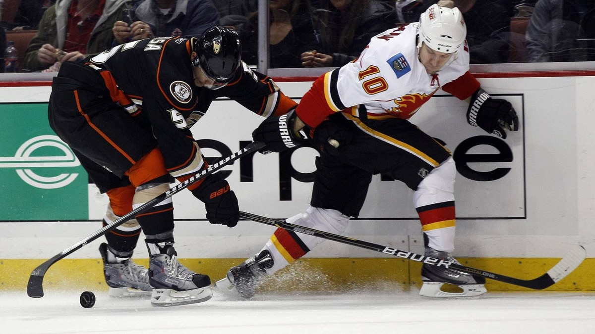Anaheim Ducks defenseman Luca Sbisa (5), of Italy, and Calgary Flames left wing Niklas Hagman (10), of Finland, battle for the puck in the first period of an NHL hockey game in Anaheim, Calif., Sunday, March 20, 2011. The Flames lost 5-4 in overtime. (AP Photo/Lori Shepler)
