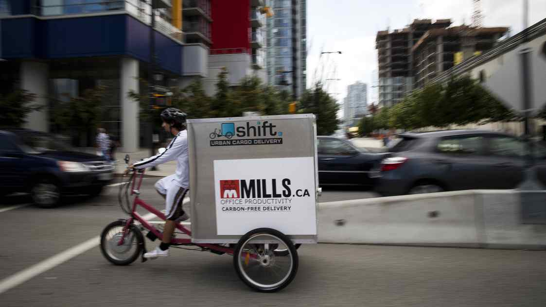 Graham Anderson, an employee at Shift Urban Cargo Delivery, rides a cargo bicycle to pick up packages to deliver in downtown Vancouver, Aug. 8, 2011.