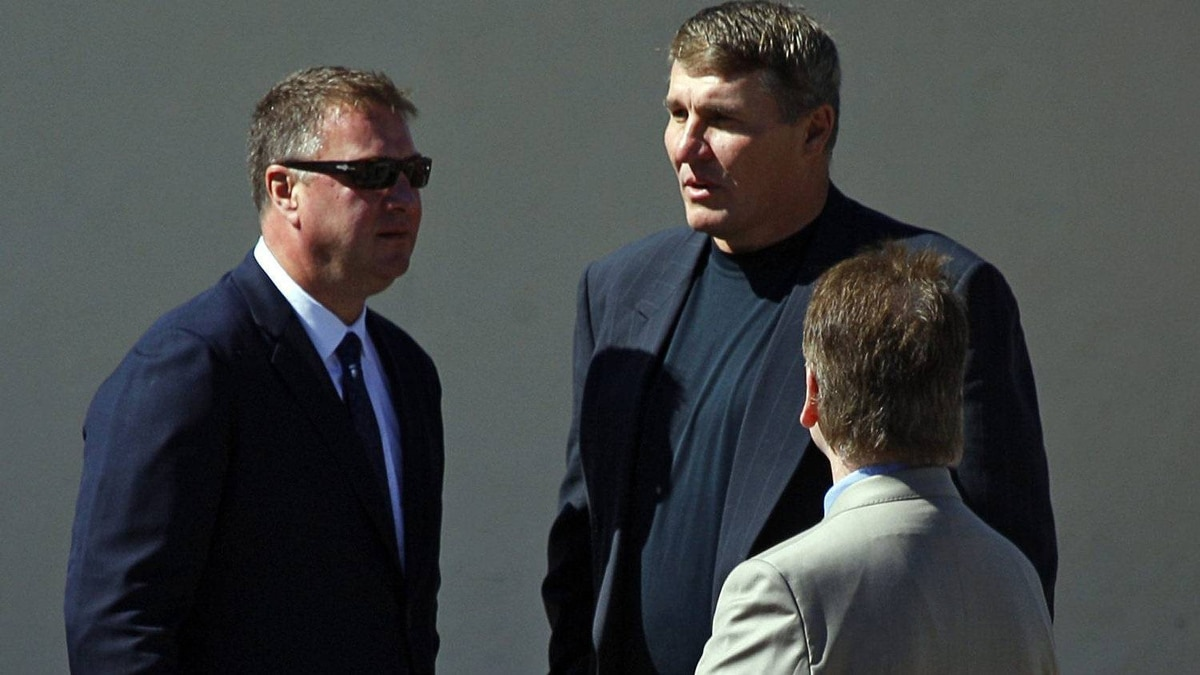 Former NFL quarterback Mark Rypien, centre, talks with Vancouver Canucks general manager Mike Gillis, while attending the funeral service for his cousin Rick Rypien, 27, in Blairmore, Alta., Saturday, Aug. 20, 2011. Rypien was found dead in his off-season Coleman, Former NFL quarterback Mark Rypien, centre, talks with Vancouver Canucks general manager Mike Gillis, while attending the funeral service for his cousin Rick Rypien. THE CANADIAN PRESS/Jeff McIntosh