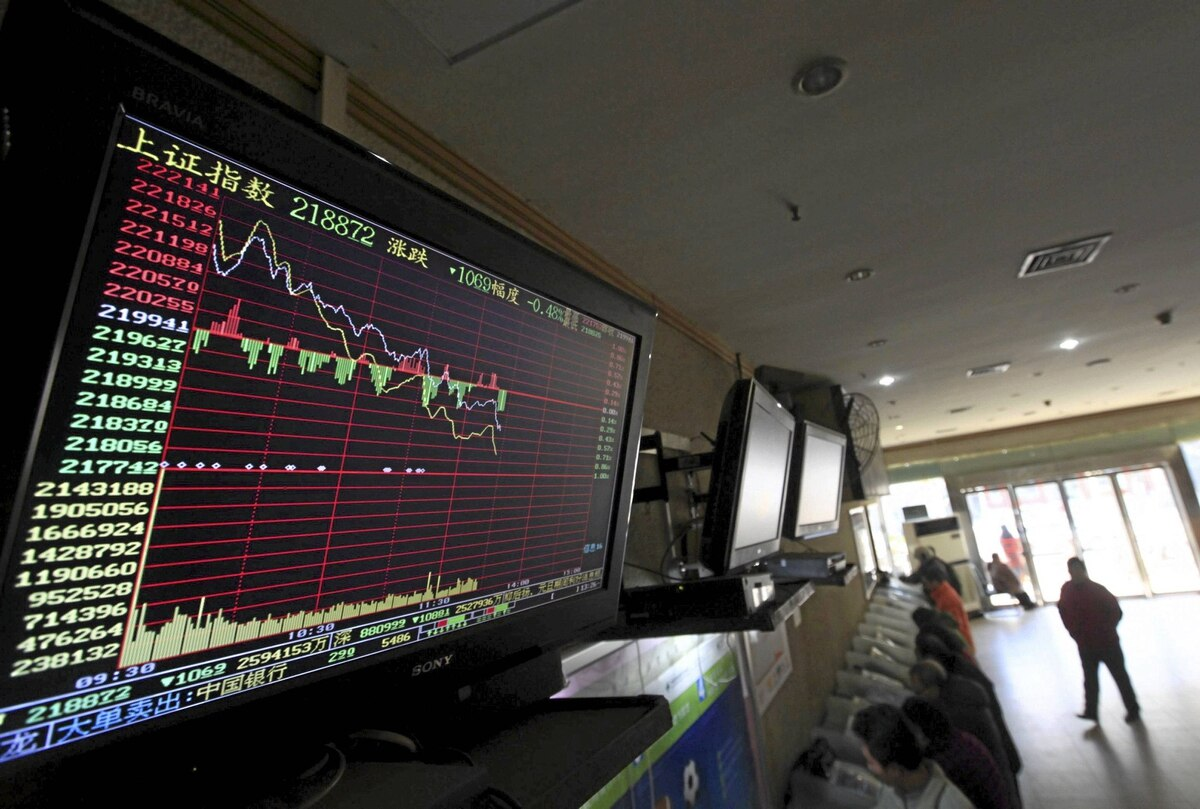 An electronic board showing stock information is seen above investors at a brokerage house in Wuhan, Hubei province January 4, 2012. China shares started the new year weaker on Wednesday, dragged down by more cyclical sectors after the Chinese premier warned of difficult economic conditions in the first quarter, hinting there will not be another massive fiscal stimulus program.