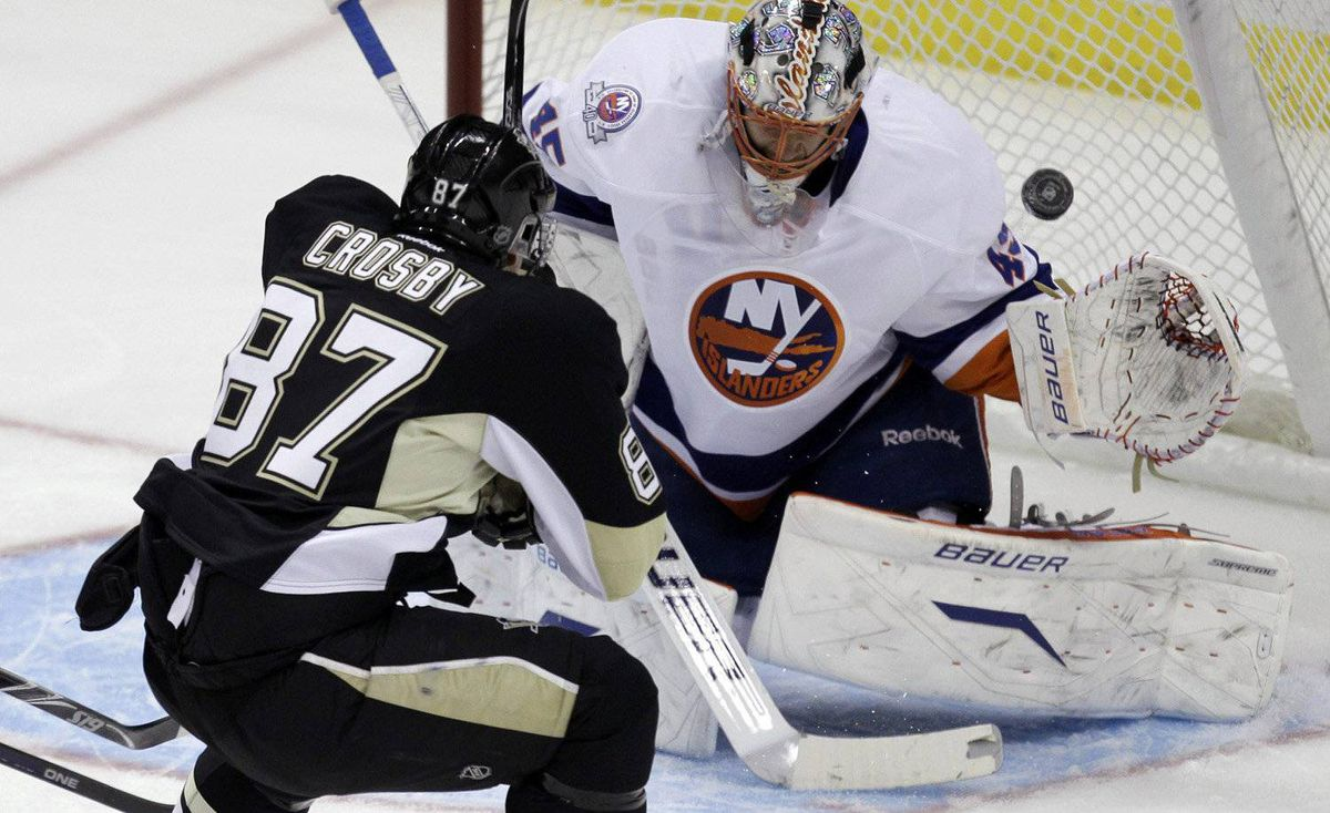 Pittsburgh Penguins' Sidney Crosby scores a first-period goal over New York Islanders goalie Anders Nilsson during an NHL hockey game in Pittsburgh on Monday, Nov. 21, 2011.