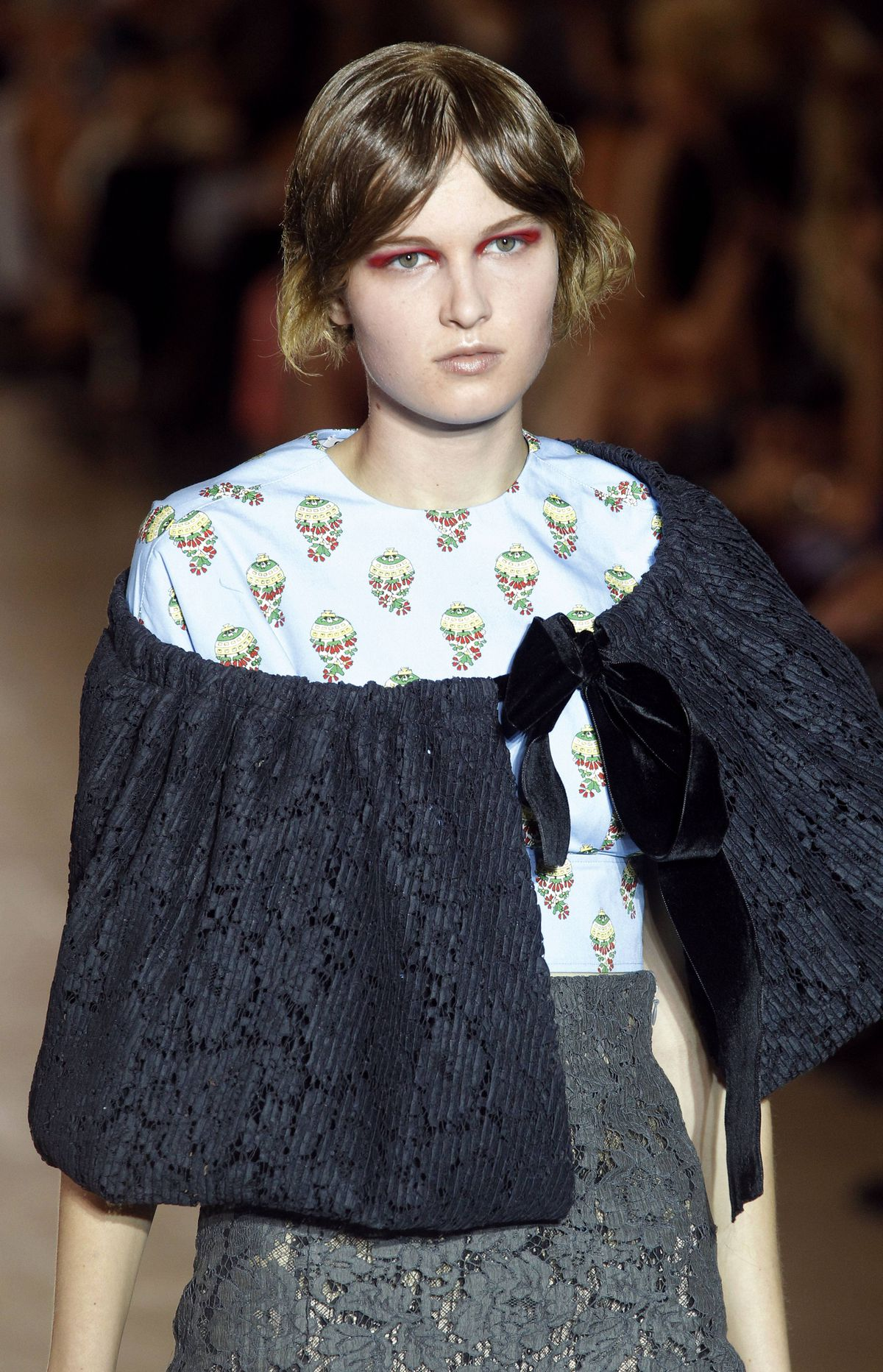Miu Miu Spring/Summer 2012 ready-to-wear collection Miu Miu is the second collection designed by Miuccia Prada and has often been considered Prada's younger, quirky sister. The collection began uncharacteristically sedate in greys and blacks. Granted, this beribboned curtain adornment is not your average cover-up.