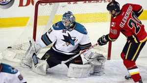 San Jose Sharks goalie Antti Niemi, left, watches Calgary Flames' Curtis Glencross shot go wide.