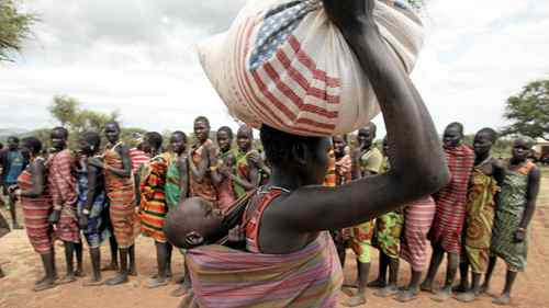 A woman from the Dadinga tribe carries food aid distributed by World Food Program (WFP) staff in the village of Lauro in Budy county in Eastern Equatoria State, south Sudan, April 2, 2010.