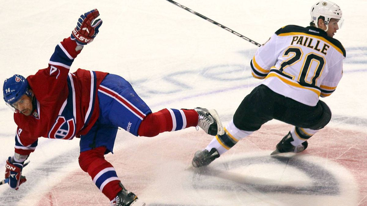 Montreal Canadiens center Tomas Plekanec (14) falls after being checked by Boston Bruins left wing Daniel Paille (20) during the second period at the Bell Centre. The Canadiens won 4-2. Jean-Yves Ahern-US PRESSWIRE