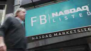 A man walks past a sign welcoming Facebook to the NASDAQ Marketsite in New York May 18, 2012.