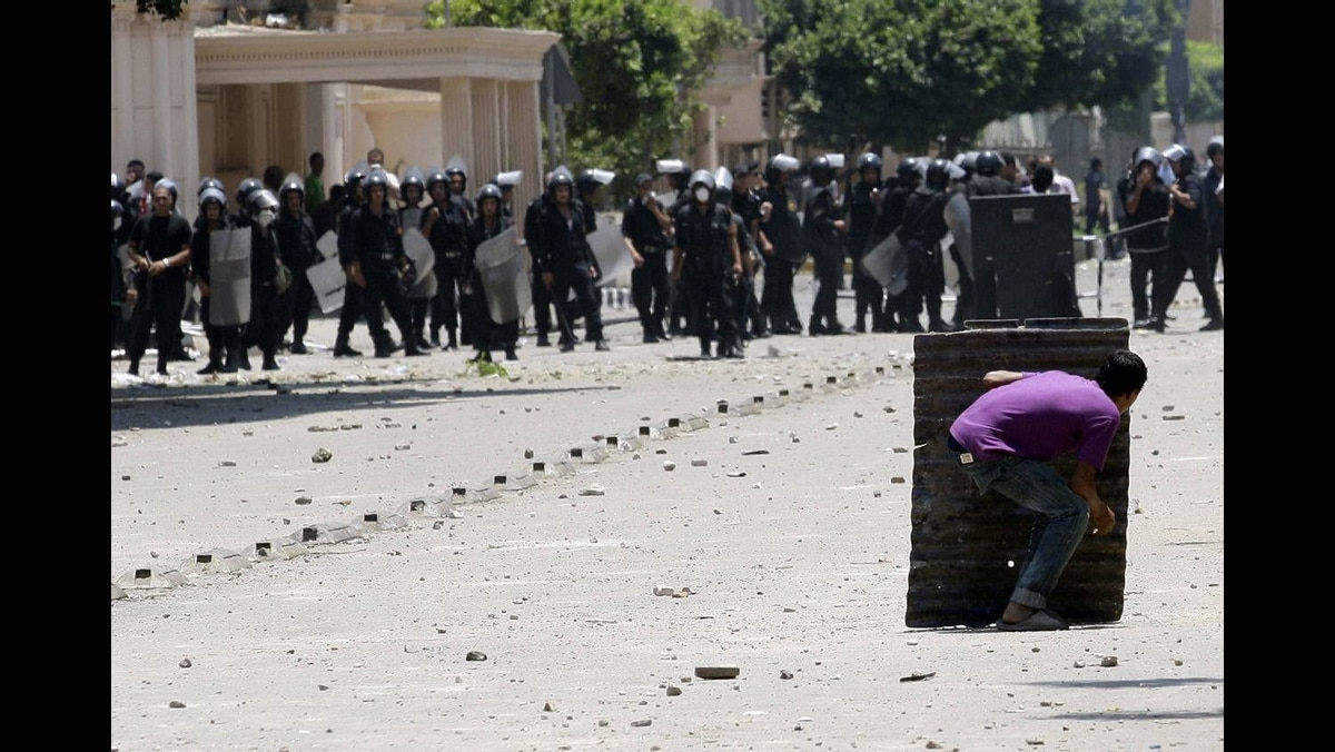 A protester takes cover during clashes with riot police in front of the Interior Ministry in Cairo June 29, 2011.