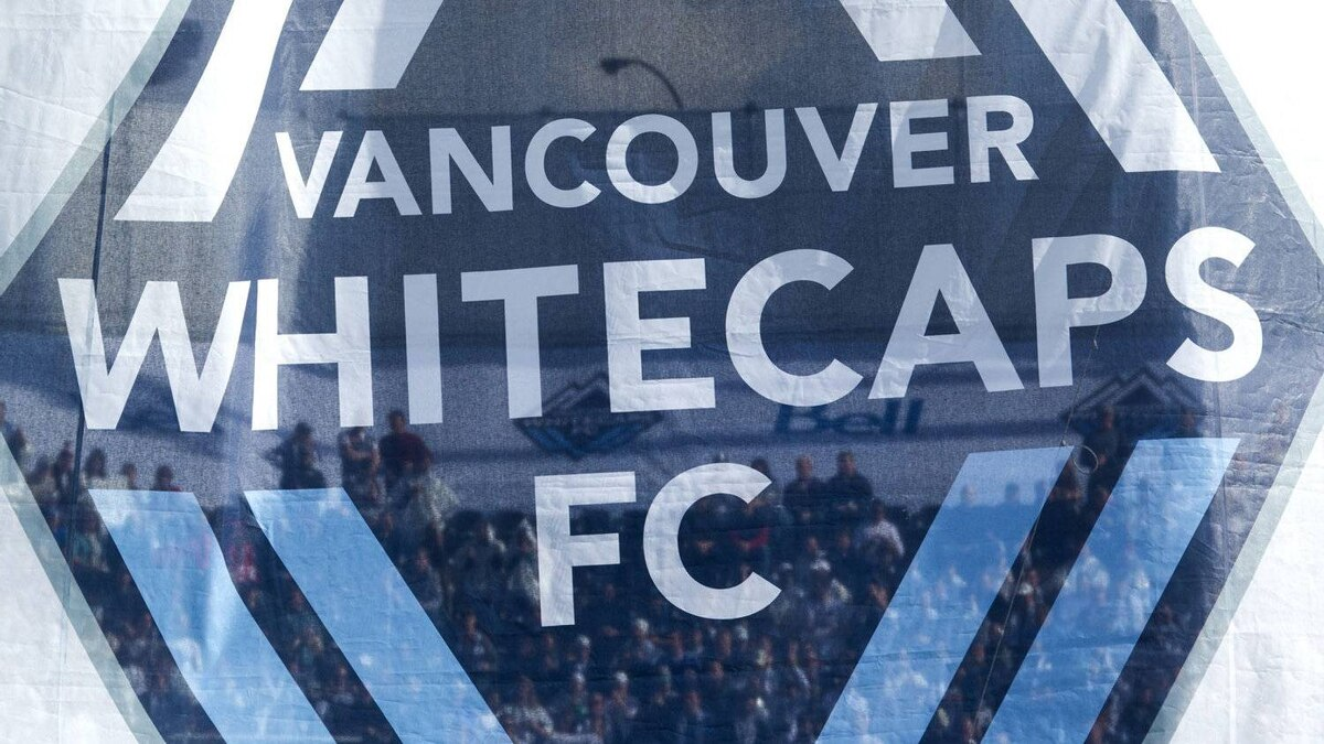 Spectators are seen through a banner prior to the Vancouver Whitecaps and Toronto FC MLS soccer game in Vancouver, B.C., on Saturday March 19, 2011.