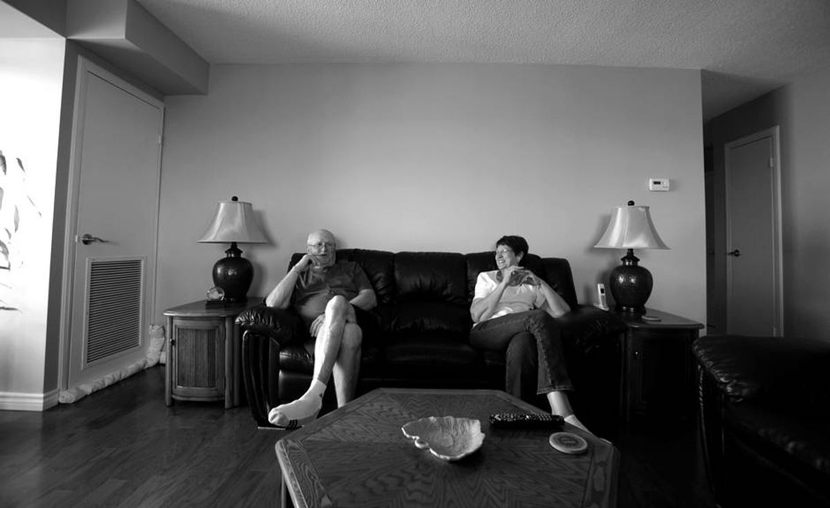 LeRoy and Catherine sit together at home in their new condo. They hope she can retire soon.