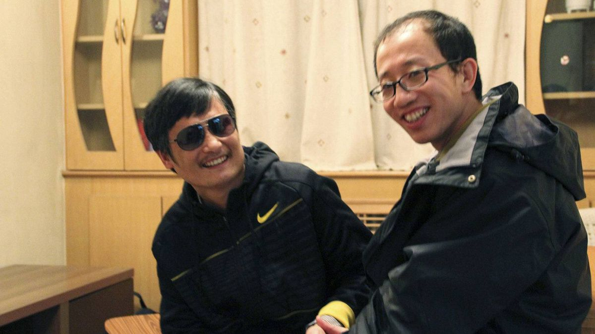 Blind legal activist Chen Guangcheng (L) and Hu Jia, one of China's most prominent dissidents, smile during a meeting, after Chen fled from house arrest, in Beijing, in this picture taken late April 2012 and released to Reuters April 28, 2012.