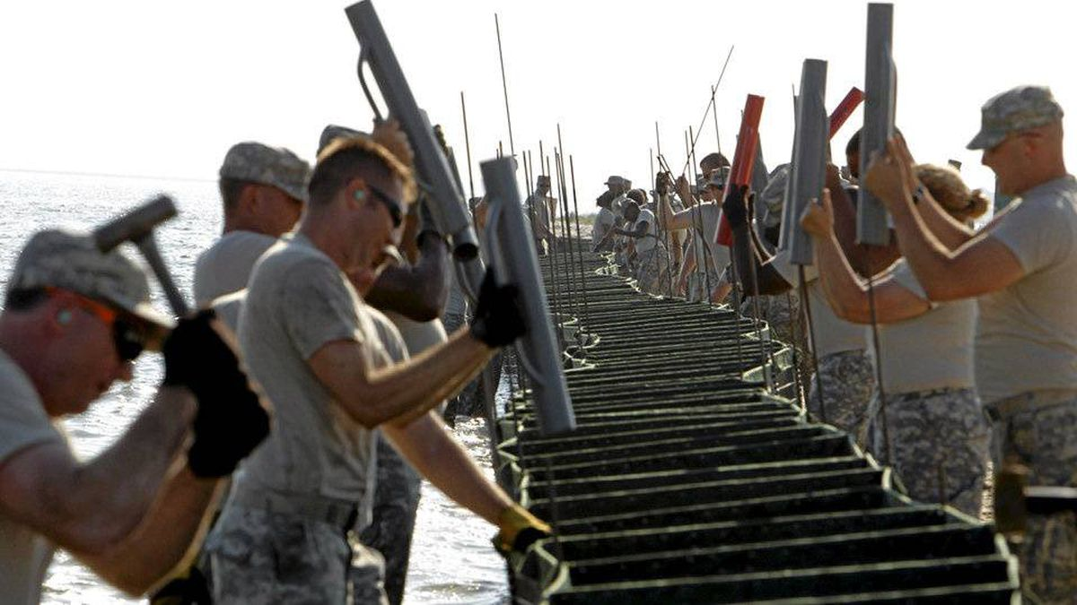 Members of the U.S. Army National Guard's 711 Brigade Support Battalion erect Hesco barriers to potentially stop any oil from damaging Dauphin Island, Alabama Wednesday. Oil spill workers raced against time in the Gulf of Mexico, hoping to take advantage of another day of calm seas in their fight to contain a huge spreading oil slick before it hits the U.S. shoreline. REUTERS/Brian Snyder