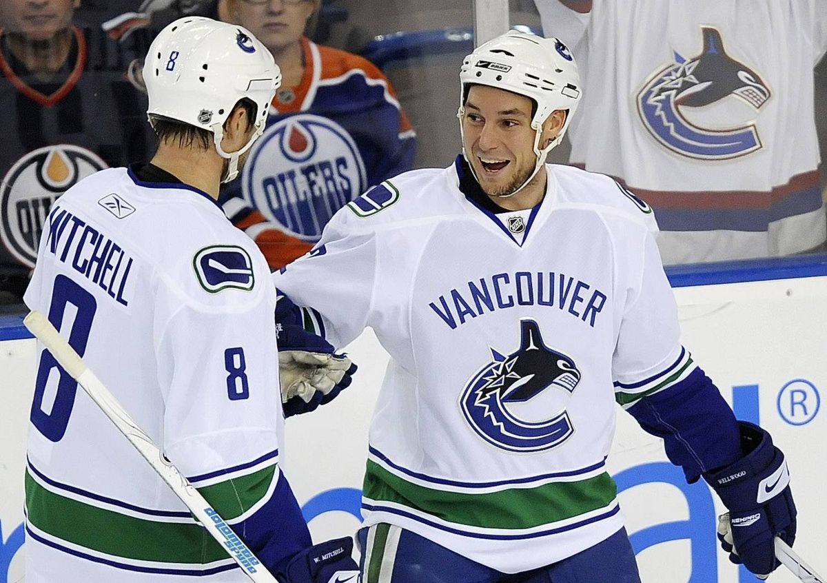 Vancouver Canucks defenseman Willie Mitchell comes over to celebrate a goal by Kyle Wellwood during a preseason hockey game in Edmonton, Alberta on Sunday, September 27, 2009.