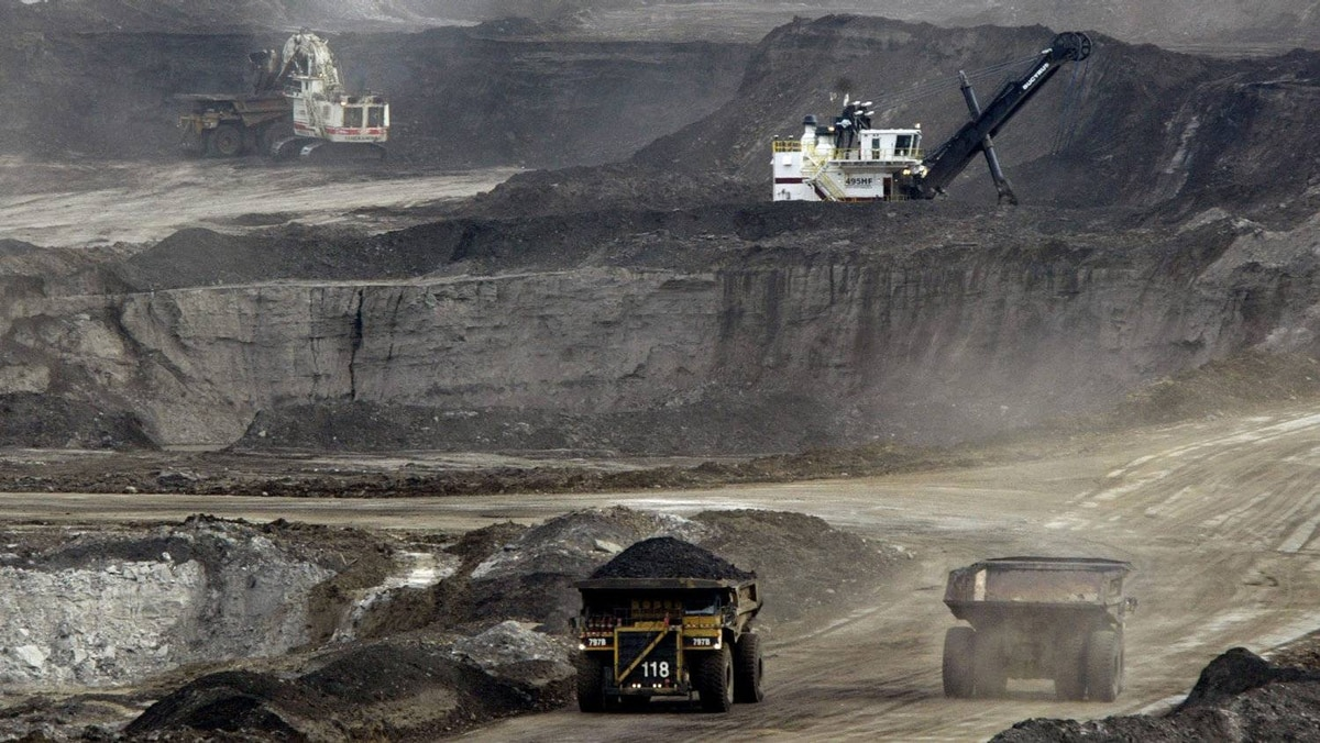 Mining trucks carry loads of oil laden sand after being loaded by huge shovels at the Albian Sands oils sands project in Ft. McMurray, Alberta, Canada.