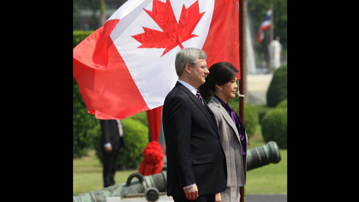 Prime Minister Stephen Harper and Thai Prime Minister Yingluck Shinawatra listen to national anthems during a welcome ceremony at Government House in Bangkok on March 23, 2012.
