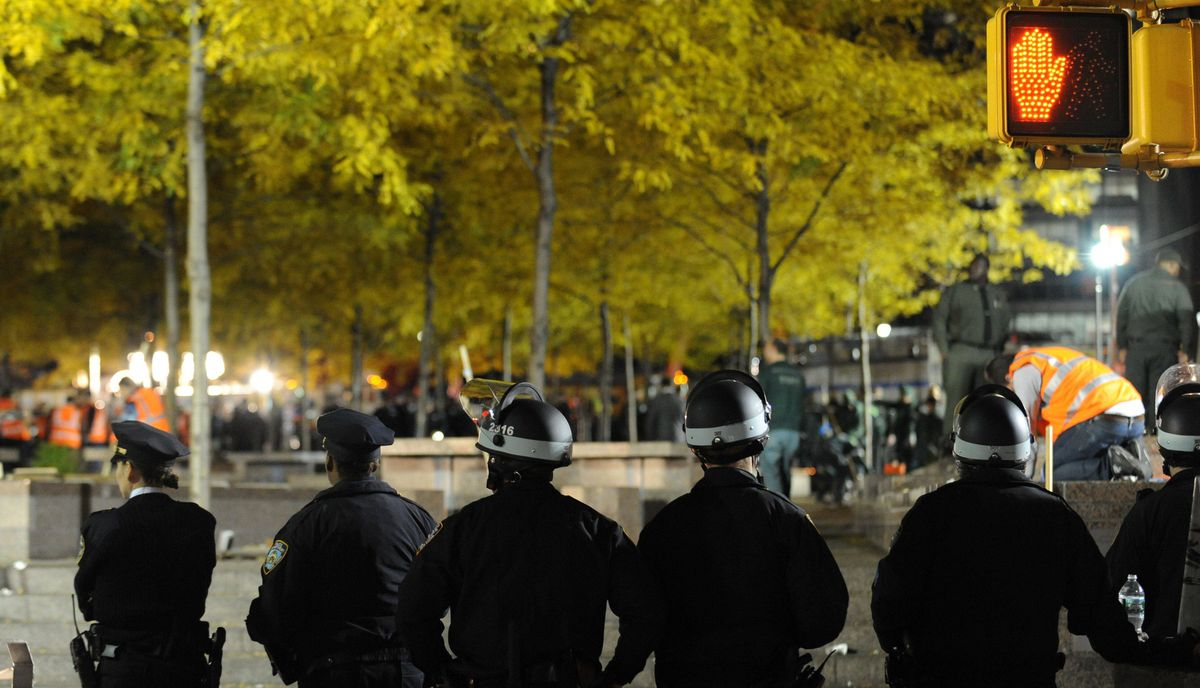 New York Police Department officers watch sanitation crews clean Zuccotti Park after city officials evicted the 'Occupy Wall Street' protest from the park in the early morning hours of November 15, 2011 in New York.