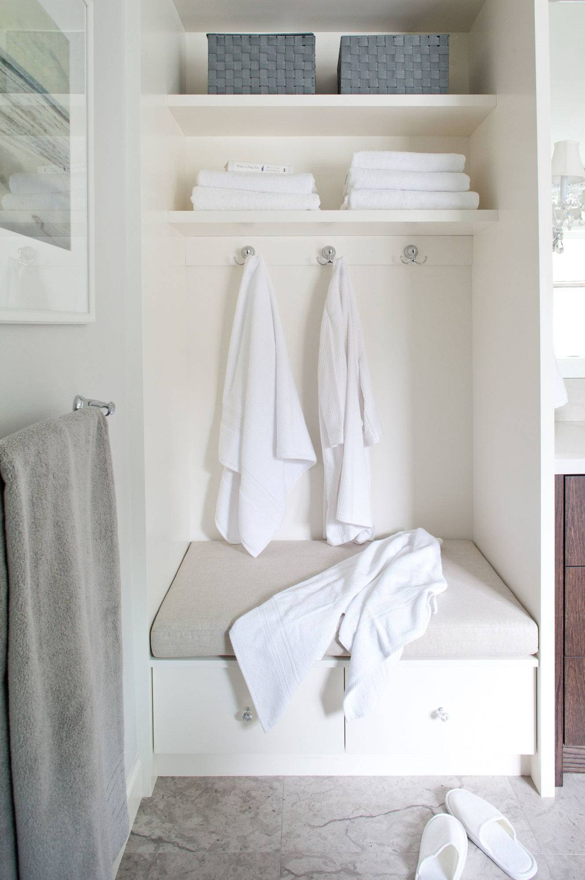 Across from the steam shower is a cabinetry tower with a bench seat, two drawers and open storage overhead for fresh linens.