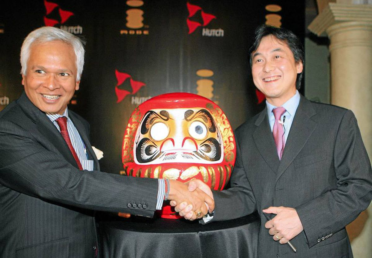 New Delhi, INDIA: Senior Vice President and Managing Director of Multimedia services at NTT DoCoMo Inc. Takeshi Natsuno (R) shakes hands with Managing Director of Hutchison Essar Mobile, Asim Ghosh in front of a Japan's Darum doll during a launch function in New Delhi, 15 December 2006.
