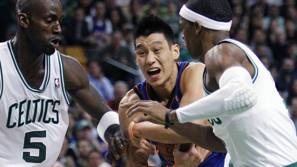 New York Knicks' Jeremy Lin, centre, holds on to the ball between Boston Celtics' Kevin Garnett (5) and Rajon Rondo in the fourth quarter of an NBA basketball game in Boston.