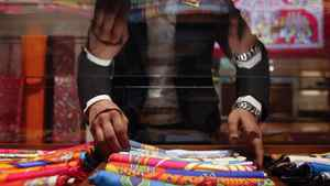 A saleswoman arranges scarves inside a Hermes showroom in Mumbai August 23, 2011.