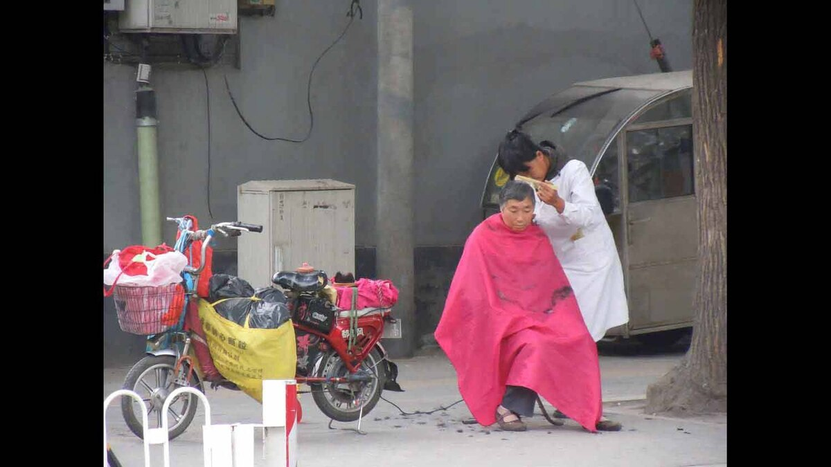She is a hairdresser on the move on the streets of Beijing. All her equipment is loaded on the little motorized bike parked next to her client!