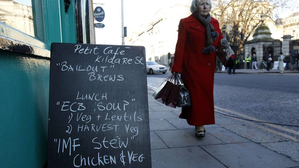 A pedestrian walks past a sign outside a cafe displaying a menu relating to the current economic climate, in Dublin November 23, 2010. The European Union urged Ireland on Tuesday to adopt an austerity budget on time to unlock promised EU/IMF funding, responding to a deepening political crisis that threatens to derail the financial rescue.