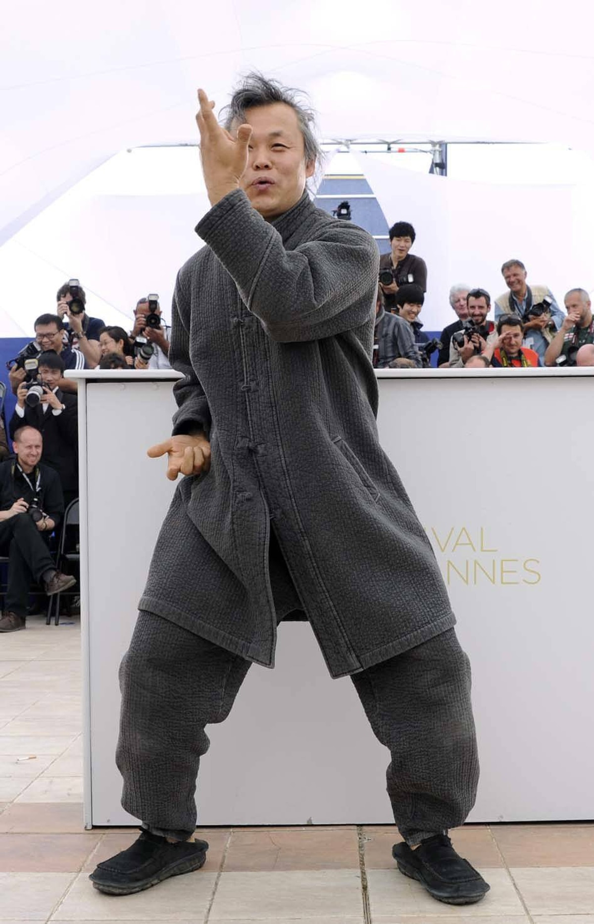 """South Korean director Kim Ki-Duk prepares to rip the heart out of the chest of a photographer during the photo call for """"Arirang"""" at the Cannes Film Festival on Friday."""