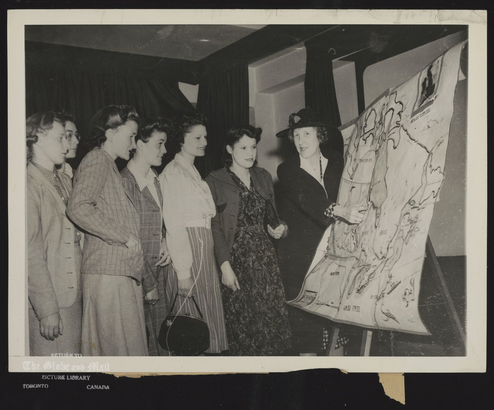 CANADIAN WAR BRIDES STUDY GEOGRAPHY. LADY TWEEDSMUIR, WIDOW OF THE LATE GOVERNOR-GENERAL OF CANADA, TEACHES CANADIAN GEOGRAPHY TO ENGLISH BRIDES OF CANADIAN SOLDIERS---A FEW OF THE MANY BRITISH GIRLS WHO HAVE MARRIED MEMBERS OF THE CANADIAN ARMED FORCES. CLASSES ARE CONDUCTED AT THE LONDON HEADQUARTERS OF THE CANADIAN LEGION TO FAMILIARIZE THE YOUNG WOMEN WITH THE COUNTRY IN WHICH THEY WILL LIVE. 8/6/43 [1943]