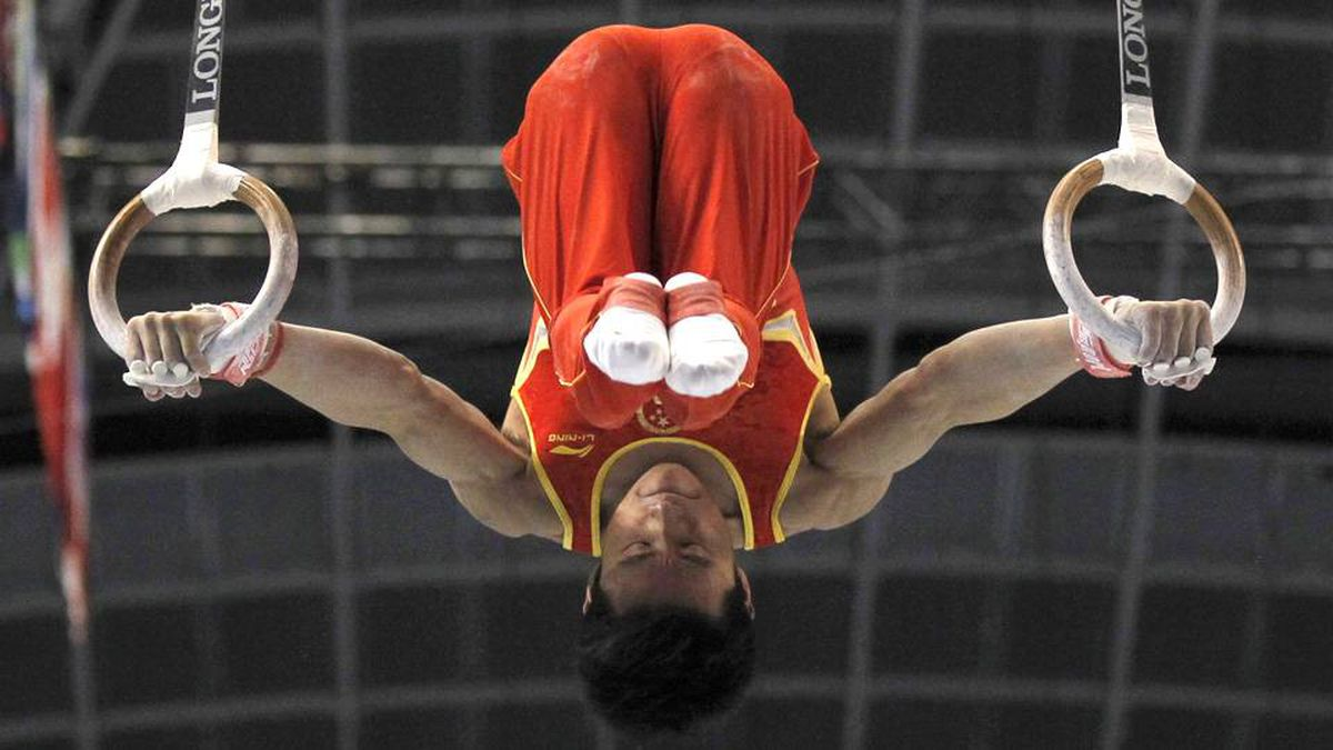 China's Teng Haibin competes on the rings during the men's team final.