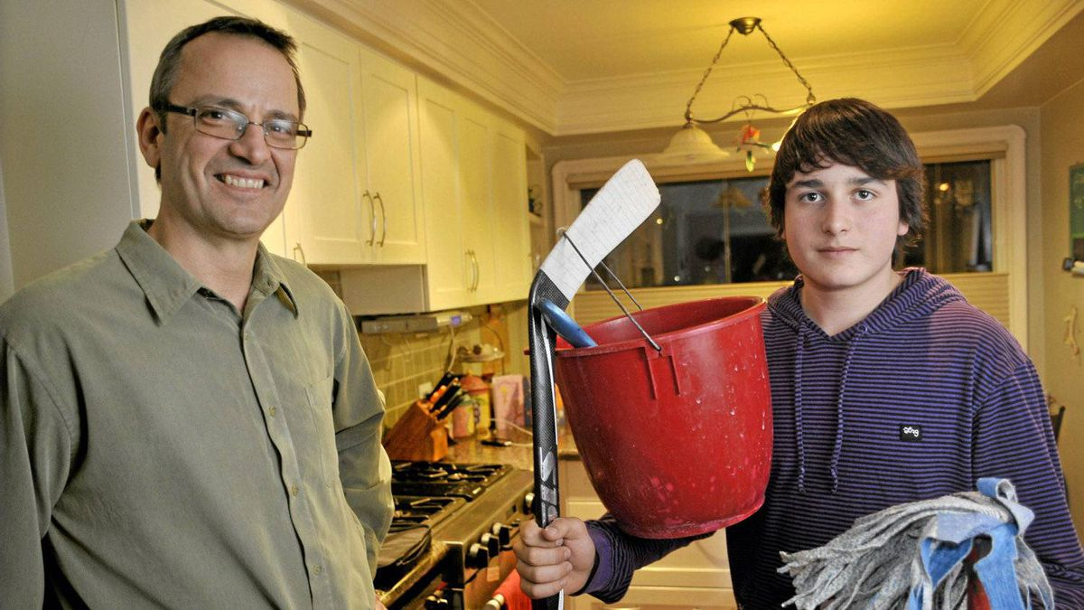 Dan Furlan, left, and his son Lukas pose in their Etobicoke home, February 18 2012. Lukas repaid his dad for his $300 hockey stick by doing house chores. (J.P. Moczulski for The Globe and Mail)