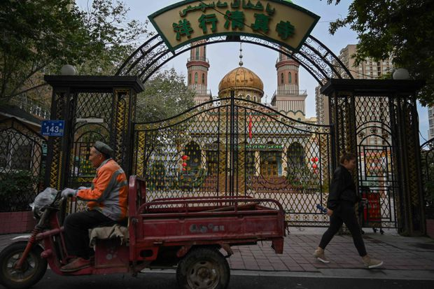 People walking past a mosque in Urumqi, the regional capital of Xinjiang, on Sept. 11, 2019.  HECTOR RETAMAL/AFP/Getty Images