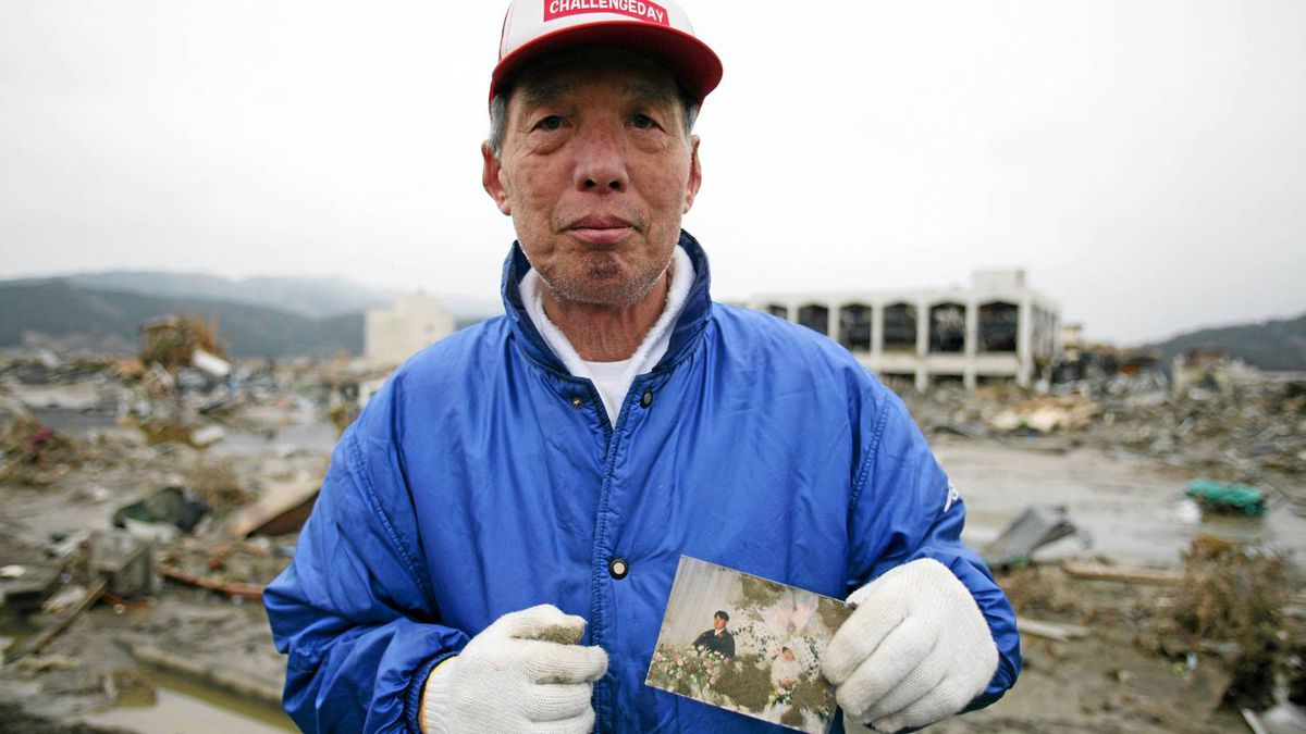 Tsuyoshi Kinno, 73, holds a picture of a missing friends son and daughter at a weddings in Rikuzen-Takaata, Miyagi Prefecture, Japan March 14, 2011. Thousands of people died in this small town 70 km north east of Sendai.