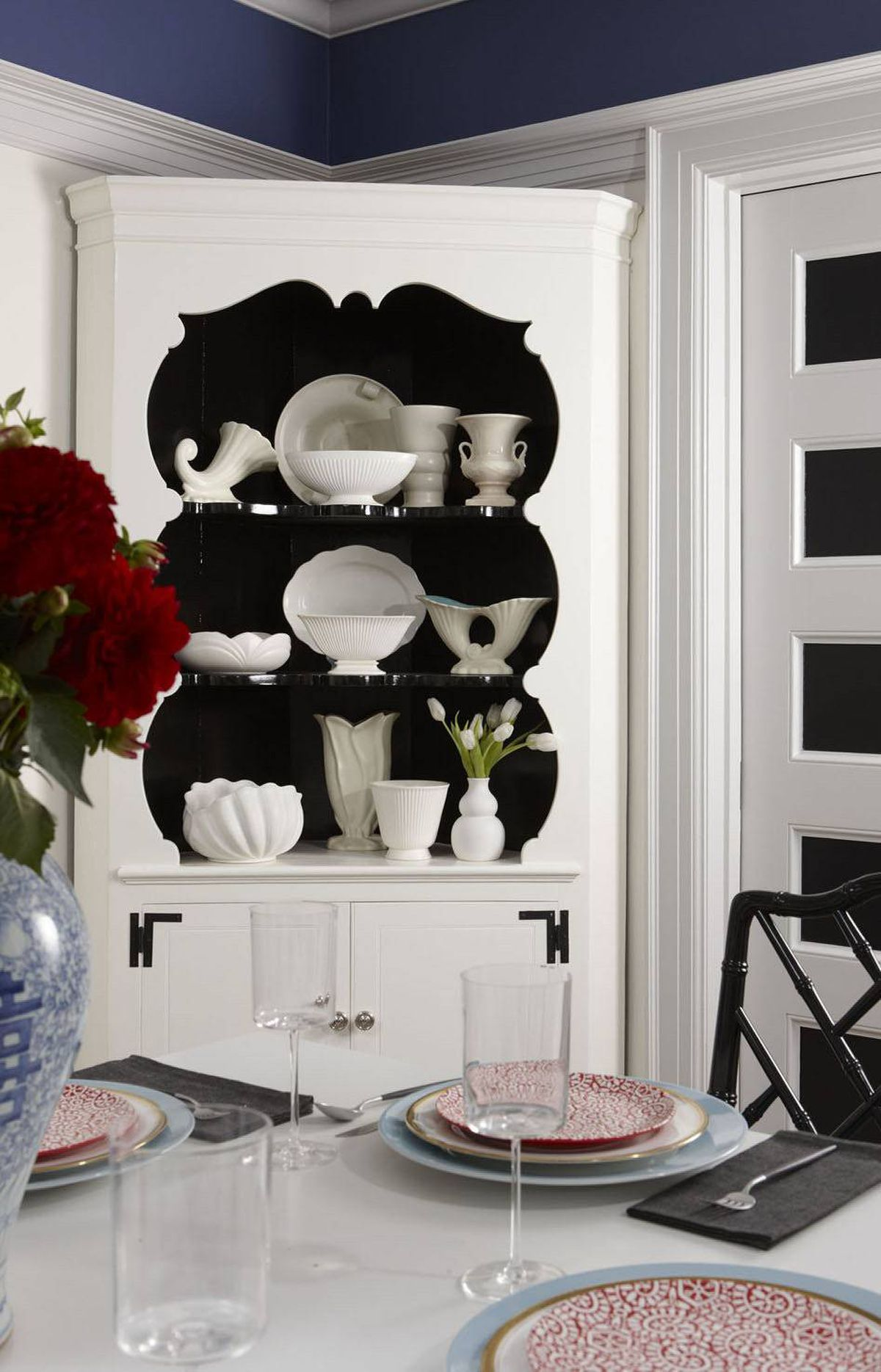 TAKE A BREAK FROM BROWN In this room, repainting wood chairs and a sideboard in glossy black injects tension into the space, provides a contrast to the light walls and table and ties in the painted details on the windows and doors. Crisp black and white always looks right!