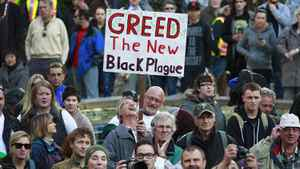 A man holds up a protest sign at the Vancouver Art Gallery as thousands of people participate in the Occupy Vancouver protest on October 15, 2011 in Vancouver, British Columbia, Canada. )