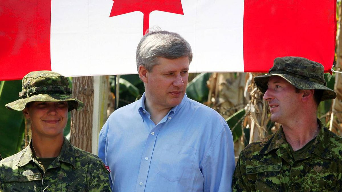 Prime Minister Stephen Harper, centre, talks with members of the Canadian Armed Forces running a Canadian water purification site in the earthquake stricken town of Jacmel on Feb. 16, 2010.